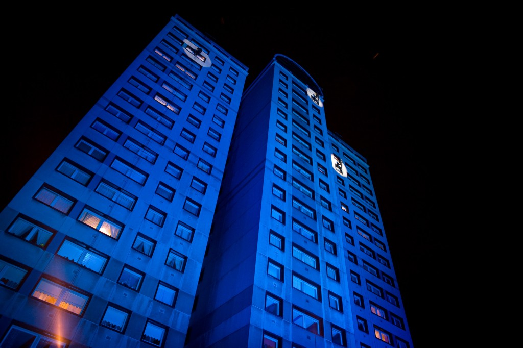 Home Glasgow by John Tiffany, for the National Theatre of Scotland. Three abseilers come down the side of a block of flats in Glasgow for the inaugural NTS performance in Glasgow. Filming a performance in different flats as the pass, which is projected onto a screen via a live feed onto a screen at the foot of the flats.