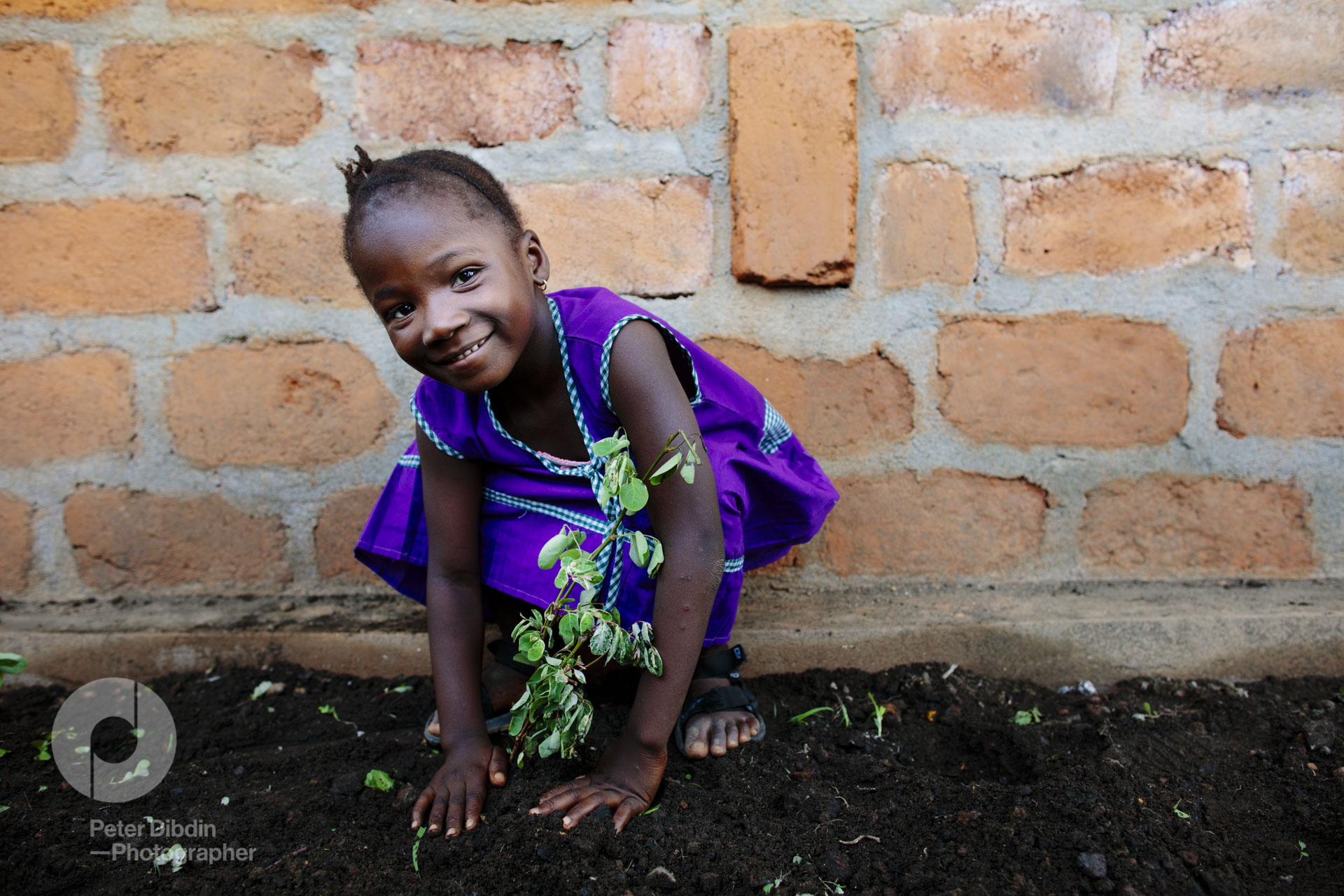 Girl planting her plant at Swawou School