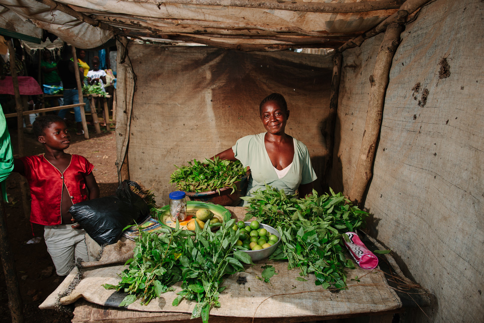 Selling limes and casava leaves in the market